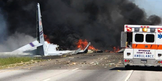 FILE - In this Wednesday, May 2, 2018 file photo, flames and smoke rise from an Air National Guard C-130 cargo plane after it crashed near Savannah, Ga. Investigators say the cause of the military plane crash that left nine people dead was pilot error. Nine airmen from the Puerto Rico National Guard died when the plane plunged onto Georgia Highway 21 shortly after takeoff from the Savannah airport. (James Lavine via AP, File)