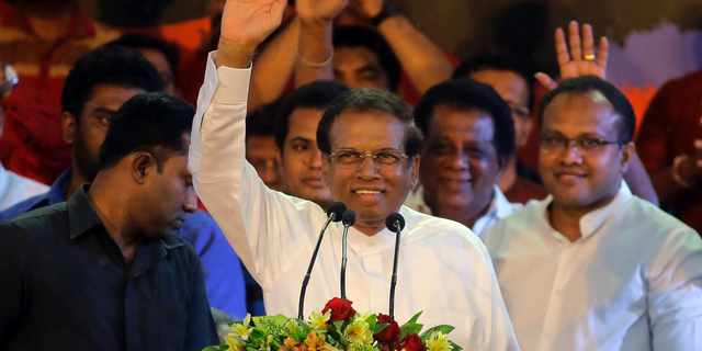 FILE - In this Nov. 5, 2018, file photo, Sri Lankan President Maithripala Sirisena, center, waves to supporters during a rally outside the parliamentary complex in Colombo, Sri Lanka. Sirisena on Friday, Nov. 9, 2018 dissolved Parliament and called for fresh elections amid a deepening political crisis. (AP Photo/Eranga Jayawardena, File)