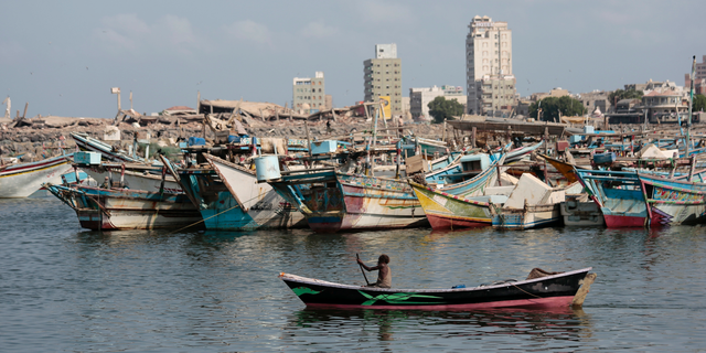 FILE - In this Friday Sept. 28, 2018 file photo, a fisherman paddles his boat past destroyed buildings on the coast of the port city of Hodeida, Yemen. Amnesty International said warned late Wednesday. Nov. 7, 2018 that Yemen's rebels have taken up positions on a hospital rooftop in the contested Red Sea city of Hodeida that a Saudi-led coalition is trying to capture. This raises concerns the Shiite rebels, known as Houthis, plan to use the patients at the Hodeida hospital as human shields to ward off airstrikes from the coalition. Amnesty is urging the warring sides to protect civilians. (AP Photo/Hani Mohammed, File)