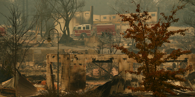 A fire truck drives through an area burned in the wildfire, Tuesday, Nov. 13, 2018, in Paradise, Calif. Five days after flames all but obliterated the Northern California town, officials were unsure of the exact number of missing. But the death toll was almost certain to rise. (AP Photo/John Locher)
