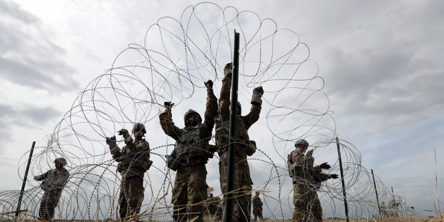 FILE - In this Sunday, Nov. 4, 2018 file photo, members of a U.S Army engineering brigade place concertina wire around an encampment for troops, Department of Defense and U.S. Customs and Border Protection personnel near the U.S.-Mexico International bridge in Donna, Texas. (AP Photo/Eric Gay)