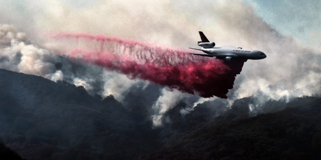 A firefighting DC-10 makes a fire retardant drop over a wildfire in the mountains near Malibu Canyon Road in Malibu, Calif. on Sunday, Nov. 11, 2018.