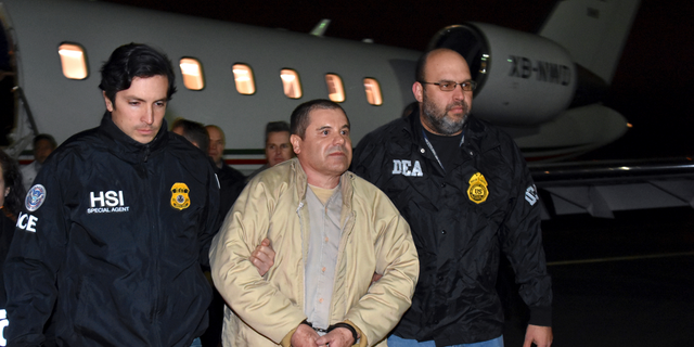 """FILE - In this Jan. 19, 2017 file photo provided U.S. law enforcement, authorities escort Joaquin """"El Chapo"""" Guzman, center, from a plane to a waiting caravan of SUVs at Long Island MacArthur Airport, in Ronkonkoma, N.Y. (U.S. law enforcement via AP, File)"""
