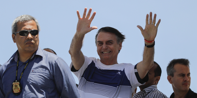 """Brazil's President-elect Jair Bolsonaro waves at supporters as he arrives to watch an aerial performance by the private pilots' group """"Esquadrilha do Ceu"""" or """"Sky Squadron"""", at Barra beach in Rio de Janeiro, Brazil, Wednesday, Oct. 31, 2018. Bolsonaro appeared in public Tuesday for the first time as president-elect. He visited a church led by ultraconservative pastor Silas Malafaia and spoke briefly to the faithful on stage. """"I am sure that I am not the most capable, but God capacitates the chosen ones,"""" he said. (AP Photo/Leo Correa)"""
