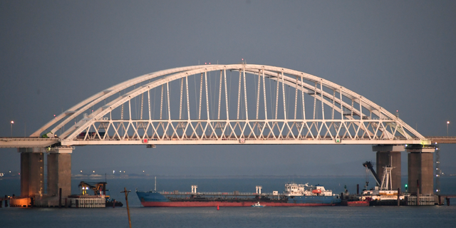 A ship under the the Kerch bridge blocks the passage to the Kerch Strait near Kerch, Crimea, Sunday, Nov. 25, 2018. Ukraine claims it siezed the Russian tanker Wednesday in a move that could put a potential prisoner swap in jeopardy. (AP Photo)