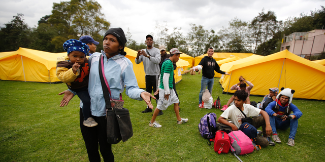 Venezuelan migrants speak to the press as they arrive to a new, refugee-style camp set up by the government in Bogota, Colombia, Tuesday, Nov. 13, 2018. Officials were initially reluctant to open camps for homeless Venezuelan arrivals but now say they have no choice as the number fleeing their nation's economic and humanitarian crisis continues to rapidly escalate. (AP Photo/Fernando Vergara)