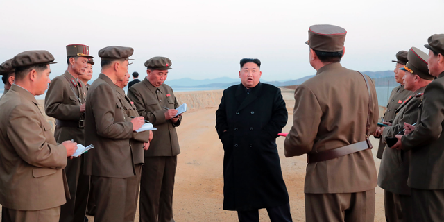 North Korean leader Kim Jong Un, center, listens to a military official as he inspects a weapon testing at the Academy of National Defense Science, North Korea. (Korean Central News Agency/Korea News Service via AP)