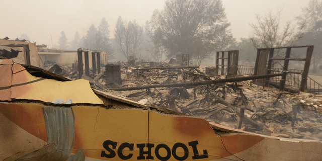 The burned remains of the Paradise Elementary school is seen Friday, Nov. 9, 2018, in Paradise, Calif. Blocks and blocks of homes and businesses in the Northern California town have been destroyed by a wildfire. Parts of the town of Paradise were still on fire on Friday.  (AP Photo/Rich Pedroncelli)
