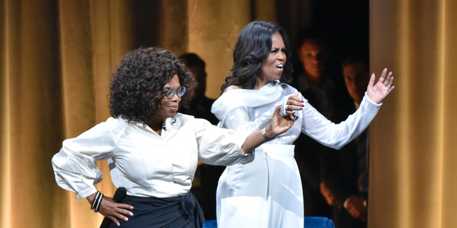 "Michelle Obama, right, is greeted by Oprah Winfrey to discusses her new book during an intimate conversation to promote ""Becoming"" at the United Center on Tuesday, Nov. 13, 2018, in Chicago. (Photo by Rob Grabowski/Invision/AP)"