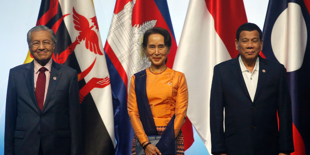 ASEAN Leaders pose for a family photo during the opening ceremony for the 33rd ASEAN Summit and Related Summits Tuesday, Nov. 13, 2018, in Singapore. From left; Prime Minister Mahathir Mohamad of Malaysia, Myanmar Leader Aung San Suu Kyi, President Rodrigo Duterte of The Philippines. (AP Photo/Bullit Marquez)