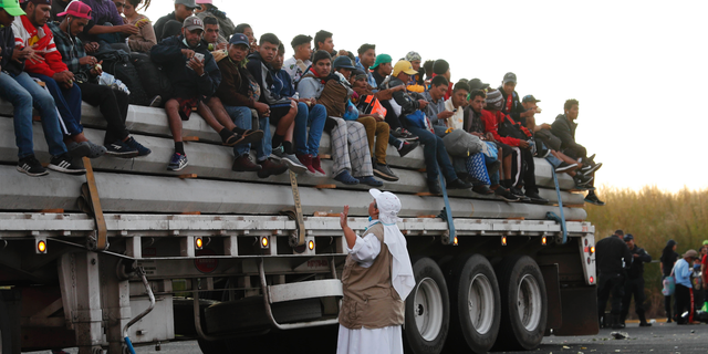 "A Catholic nun gives travel advice to Central American migrants riding in the bed of a semi-trailer, as they move toward the U.S. border, in Ixtlán del Rio, Nayarit, Mexico, Tuesday, Nov. 13, 2018. The U.S. government said it was starting work Tuesday to ""harden"" the border crossing from Tijuana, Mexico, to prepare for the arrival of a migrant caravan leapfrogging its way across western Mexico. (AP Photo/Marco Ugarte)"