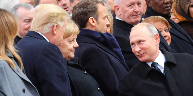 Russian President Vladimir Putin talks with German Chancellor Angela Merkel and US President Donald Trump as they attend a ceremony at the Arc de Triomphe in Paris, as part of commemorations marking the 100th anniversary of the 11 November 1918 armistice, ending World War I, Sunday, Nov. 11, 2018. (Ludovic Marin/Pool Photo via AP)