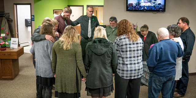 Rev. Jim Woldhuis prays with family members before entering the sanctuary for the funeral for 32-year-old Sara Schneider and her 10-year-old daughter, Haylee Hickle. The community of Chippewa Falls gathers as one Thursday, Nov. 8,2018, to mourn and remember three Girl Scouts and a mother who were run over and killed last weekend while picking up litter on a two-lane highway outside of town. Funerals for Sara Jo Schneider and her daughter Haylee Hickle were held on Thursday.  (Glen Stubbe/Star Tribune via AP)