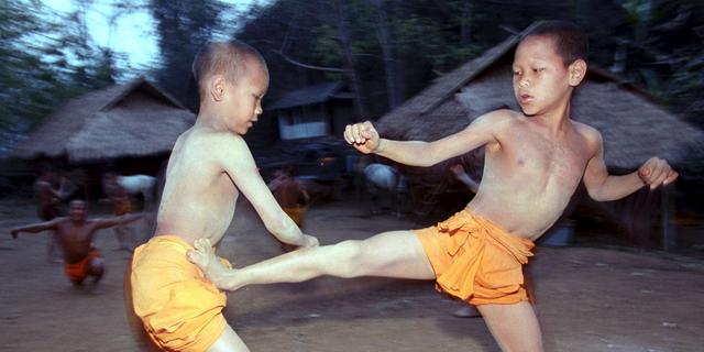 FILE - In this March 19, 2002, file photo, two novice Buddhist monks practice Muay Thai (Thai kickboxing) during a morning training session at the Golden Horse Monastery in northern Thailand. The death of a 13-year-old boy who was knocked out during a Muay Thai boxing match in Thailand has sparked debate over whether to ban child boxing. (AP Photo/David Longstreath, File)