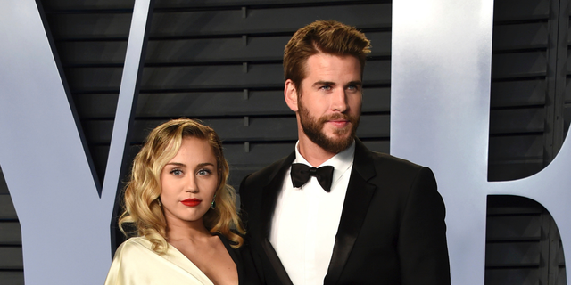 Miley Cyrus, left, and Liam Hemsworth arrive at the Vanity Fair Oscar Party in Beverly Hills, Calif. Though Cyrus and Hemsworth lost their home in the deadly wildfire blazing California, they are donating $500,000 to The Malibu Foundation through Cyrus' charity, The Happy Hippie Foundation.