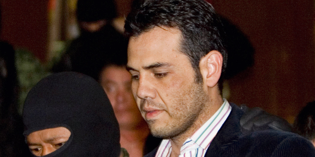 """FILE - In this March 19, 2009 file photo, military officers escort alleged drug trafficker Vicente Zambada during his presentation to the media in Mexico City. Zambada, a former top lieutenant to Joaquin """"El Chapo"""" Guzman and likely witness at the Mexican drug lord's New York trial, has pleaded guilty to trafficking conspiracy in Chicago, saying in a plea agreement unsealed Friday, Nov. 9, 2018, that he will cooperate with prosecutors in hopes of a reduced sentence and protection from cartel retribution for his family. (AP Photo/Eduardo Verdugo, File)"""