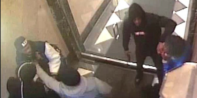 This April 3, 2018 still image from a surveillance video, provided by the U.S. Attorney's Office, Southern District of New York, was released by federal prosecutors to document alleged involvement by rapper Tekashi 6ix9ine in several violent incidents and to support their request to a judge that the rapper be denied bail. Authorities say this frame shows 6ix9nine — whose legal name is Daniel Hernandez — carrying a firearm into a building near Times Square where Hernandez and others participated in a gunpoint robbery of a rival. (U.S. Attorney's Office via AP)