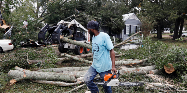 The sound of chainsaws grind through a neighborhood in Natchez, Miss., as cleanup begins following a tornado that hit early Thursday, Nov. 1, 2018. At least 11 tornadoes have been confirmed by National Weather Service surveyors so far in Louisiana and Mississippi as part of a storm system that moved across the region Wednesday night and Thursday. (AP Photo/Rogelio V. Solis)