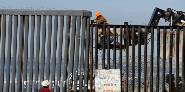 A man on the U.S. side of the border, top, works on the border structure as a man standing on the beach looks on, seen from Tijuana, Mexico, Thursday, Nov. 15, 2018. Members of a migrant caravan from Central America continued to arrive by the hundreds in the Mexican border city of Tijuana. (AP Photo/Gregory Bull)
