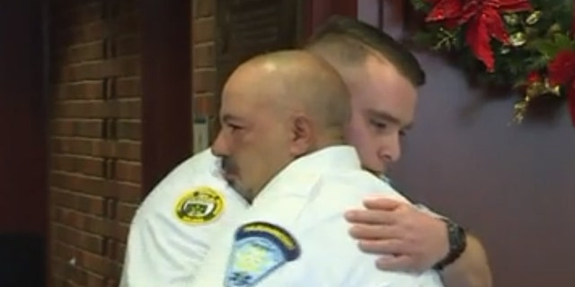 EMT partners Chris Cabral and Ray Berwick embrace at a ceremony celebrating Berwick's actions that helped save Cabral following his stroke.