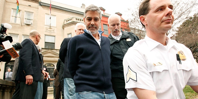 Actor George Clooney is arrested for civil disobedience after protesting at the Sudan Embassy in Washington on March 16, 2012. Clooney was protesting the escalating humanitarian crisis in Sudan. REUTERS/Kevin Lamarque (