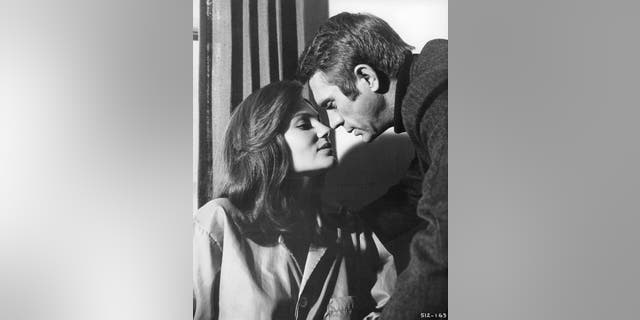"Jacqueline Bisset leans forward to kiss Steve McQueen in a scene from the film ""Bullitt."" — Getty"