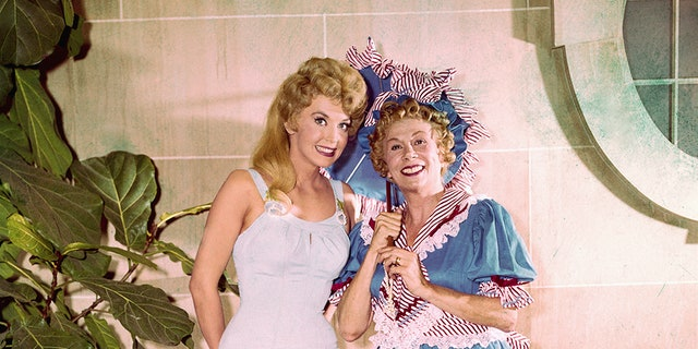"""Photograph from """"The Beverly Hillbillies"""" with Bea Benaderet (right) in an 1890's bathing suit costume, as cousin Pearl Bodine. She stands next to Donna Douglas, as Elly May Clampett, in a one-piece bathing suit."""