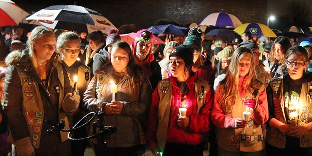 Girl Scouts sing as hundreds of community members turn out in the rain Sunday evening, Nov. 4, 2018, for a candlelight vigil at Halmstad Elementary School in Chippewa Falls, Wis.