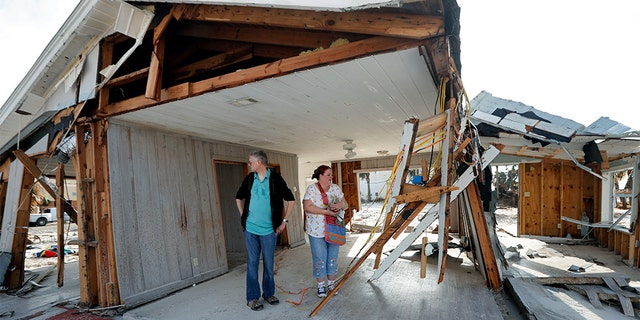 Lanie Eden and her husband Ron stand in the destroyed vacation home they rented every year as they look for their possessions in the aftermath of Hurricane Michael in Mexico Beach, Fla. The region in the battleground state is still trying to recover from Michael, which pummeled several counties in the Florida Panhandle and was responsible for dozens of deaths, and among the ruins are polling stations in a GOP mainstay. (AP Photo/Gerald Herbert, File)