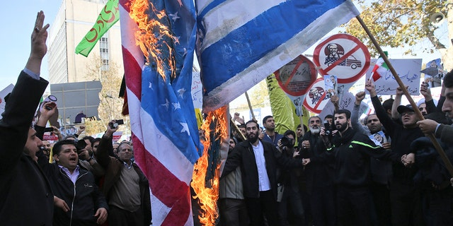 Iranian demonstrators burn representations of the U.S. and Israeli flags during a rally in front of the former U.S. Embassy in Tehran, Iran, on Sunday, Nov. 4, 2018.