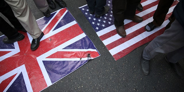 Representations of the U.S. and British flags are walked on by demonstrators during an annual rally in front of the former U.S. Embassy in Tehran, Iran, on Sunday, Nov. 4, 2018.