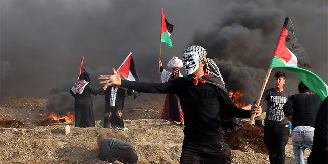 Protesters wave their national flags while others burn tires near the fence of Gaza Strip border with Israel during a protest east of Gaza City, Friday, Nov. 9. Gaza's Hamas rulers said Friday that deadly protests along Gaza-Israel perimeter fence have achieved some goals; $15 million from Qatar to help pay the salaries of civil servants. (AP Photo/Adel Hana)