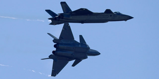 Two J-20 stealth fighter jets of the Chinese People's Liberation Army (PLA) Air Force perform during the 12th China International Aviation and Aerospace Exhibition.