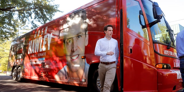 Missouri Attorney General and Republican U.S. Senate candidate Josh Hawley steps off his campaign bus to speak to supporters during a stop Tuesday, Oct. 23, 2018, in Ballwin, Mo. Hawley is seeking to unseat Democratic incumbent Sen. Claire McCaskill. (AP Photo/Jeff Roberson)