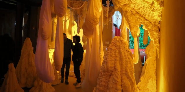 Kareem Rahma, right, founder and CEO of the Nameless Network and co-creator of The Museum of Pizza appears in an art installation in New York.