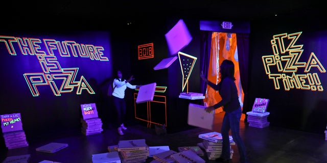"A pizza box playroom created with neon lights and colorful fluorescent tape called ""Gazoo,"" is part of a group art exhibition celebrating pizza."