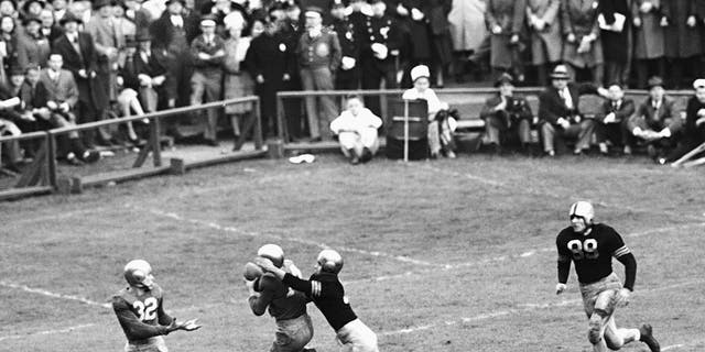 FILE - In this Nov. 9, 1946, file photo, Notre Dame's Emil Sitko grabs a pass intended for Army's Bill West, center right, during the fourth quarter of a college football game at Yankee Stadium in New York.