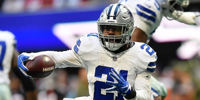 Dallas Cowboys running back Ezekiel Elliott (21) moves past Atlanta Falcons strong safety Damontae Kazee (27) on his way to a touchdown during the second half of an NFL football game, Sunday, Nov. 18, 2018, in Atlanta.