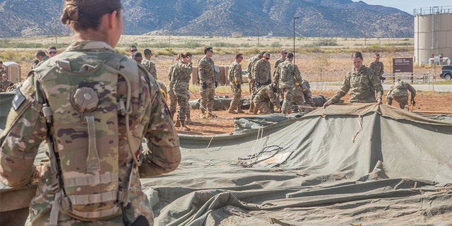 U.S. Army soldiers, assigned to 309th Military Intelligence Battalion and 305th Military Intelligence Battalion, positioning a tent on Fort Huachuca, Arizona.