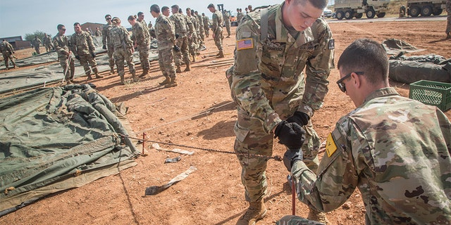 U.S. Army soldiers, assigned to 309th Military Intelligence Battalion and 305th Military Intelligence Battalion, working together to hammer a stake into the ground while setting up tents on Fort Huachuca, Arizona, on Thursday.