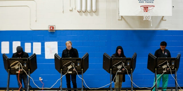 Across the country, voters headed to the polls Tuesday in one of the most high-profile midterm elections in years. (AP Photo/John Minchillo)