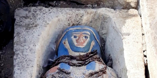 This undated photo released by the Egyptian Ministry of Antiquities on Wednesday, Nov. 28, 2018, shows an ancient mummy covered with a layer of painted cartonnage,