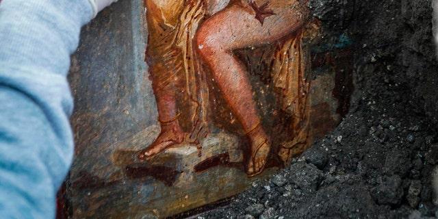An archeologist cleans up the fresco ''Leda e il cigno'' (Leda and the swan). (Cesare Abbate/ANSA via AP)