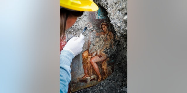 An archeologist cleans up the fresco ''Leda e il cigno'' (Leda and the swan). (Cesare Abbate/ANSA via AP)