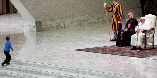 A child makes his way to the stage during Pope Francis weekly general audience, in the Paul VI Hall at the Vatican, Wednesday, Nov. 28, 2018.