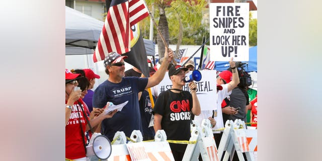 Crowd of protestors gather outside the Broward County of Supervisor of Elections Office as the statewide election recount is underway while ballots for governor, Senate, Agricultural Commission were run through scanning machines in Broward for a second time under the watchful eye of representatives of both parties and the campaigns on Sunday, Nov. 11, 2018. (Carl Juste/Miami Herald via AP)