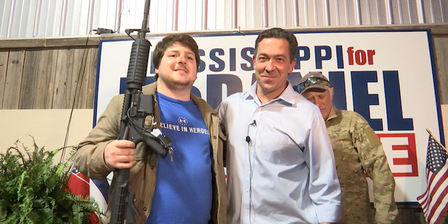 McDaniel poses with a supporter, who won the raffle for an AR-15 rifle ahead of Mississippi's special election.