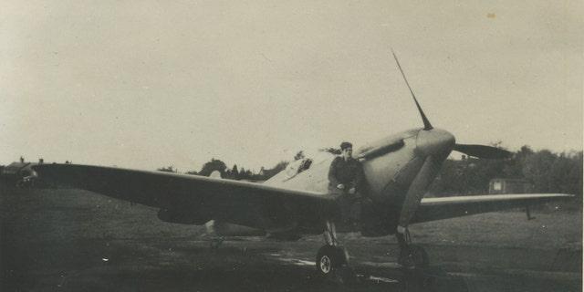 Photo of Flt. Lt. Alastair Gunn sat on a Spitfire. (Spitfire AA810 Project)