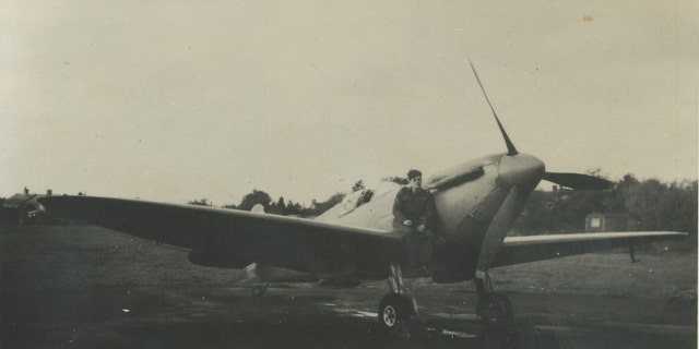 Photo of Flt. Lt. Alastair Gunn sat on a Spitfire.