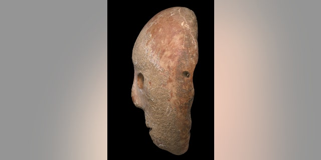 The mask dates back to the Neolithic period. (Clara Amit, Israel Antiquities Authority)